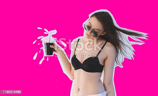 Beautiful brunette posing in lingerie with refreshing fruit juice. Cutout on vibrant pink background.