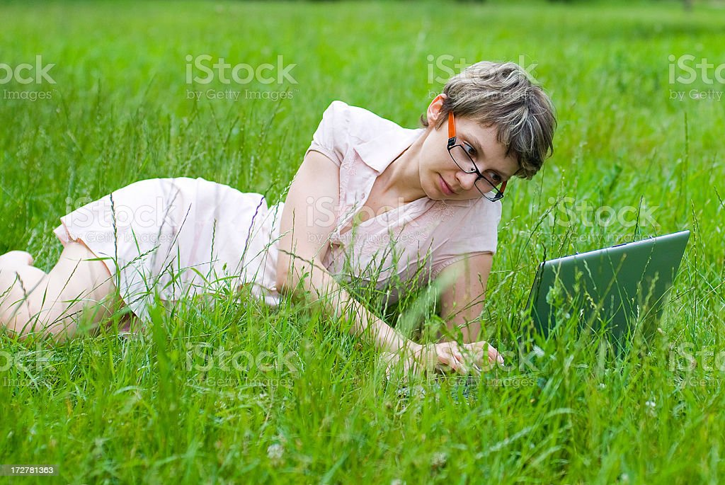 girl with laptop in park on green grass royalty-free stock photo