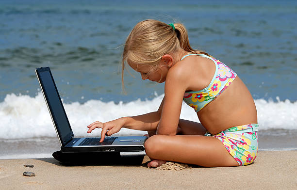 Girl with laptop on the beach stock photo