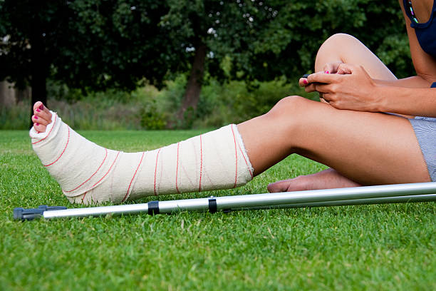 girl with leg in plaster using her smartphone - broken leg stock photos and pictures