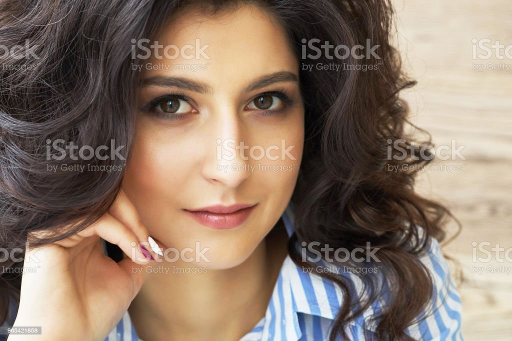 Girl with long curly hair. Perfect skin. Stylish gorgeous girl in the luxury beauty salon. Girl with long curly hair. Beautiful sexy girl with hair sitting near the window in the dressing room zbiór zdjęć royalty-free