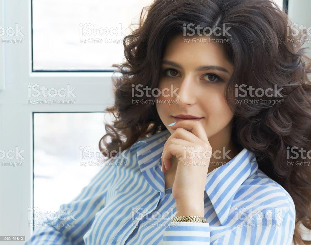 긴 곱슬 머리를 가진 소녀입니다. 세련 된 럭셔리 뷰티 살롱에서 멋진 여자입니다. 긴 곱슬 머리를 가진 소녀입니다. 드레싱 룸에 창 근처에 앉아 머리를 가진 아름 다운 섹시 한 여자 - 로열티 프리 갈색 머리 스톡 사진