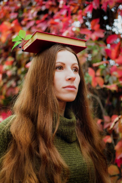 Girl with long hair holding a book on head among colorful ivy in autumn. stock photo