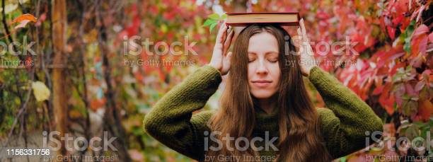 Girl with long hair holding a book on head among colorful ivy in picture id1156331756?b=1&k=6&m=1156331756&s=612x612&h=jmbldvvzmfl84 xajgn0gyisqq5e aazghdlmq3bzjk=