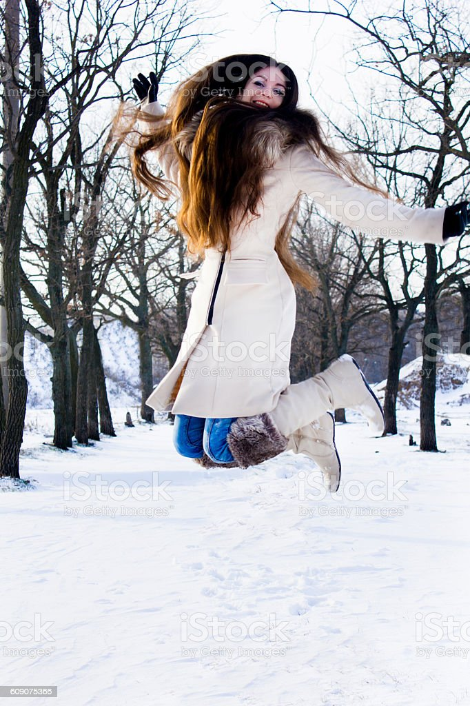 Girl with long hair jumping in the snow stock photo