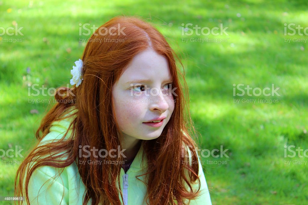 Girl with long red hair looking puzzled on garden lawn stock photo