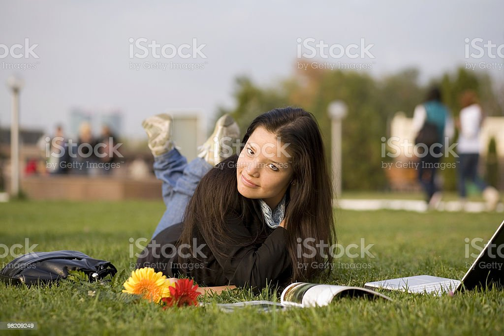 Girl with magazin and laptop on grass, campus royalty-free stock photo