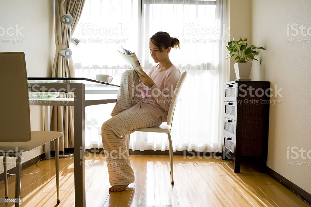 Girl with magazine at breakfast royalty-free stock photo