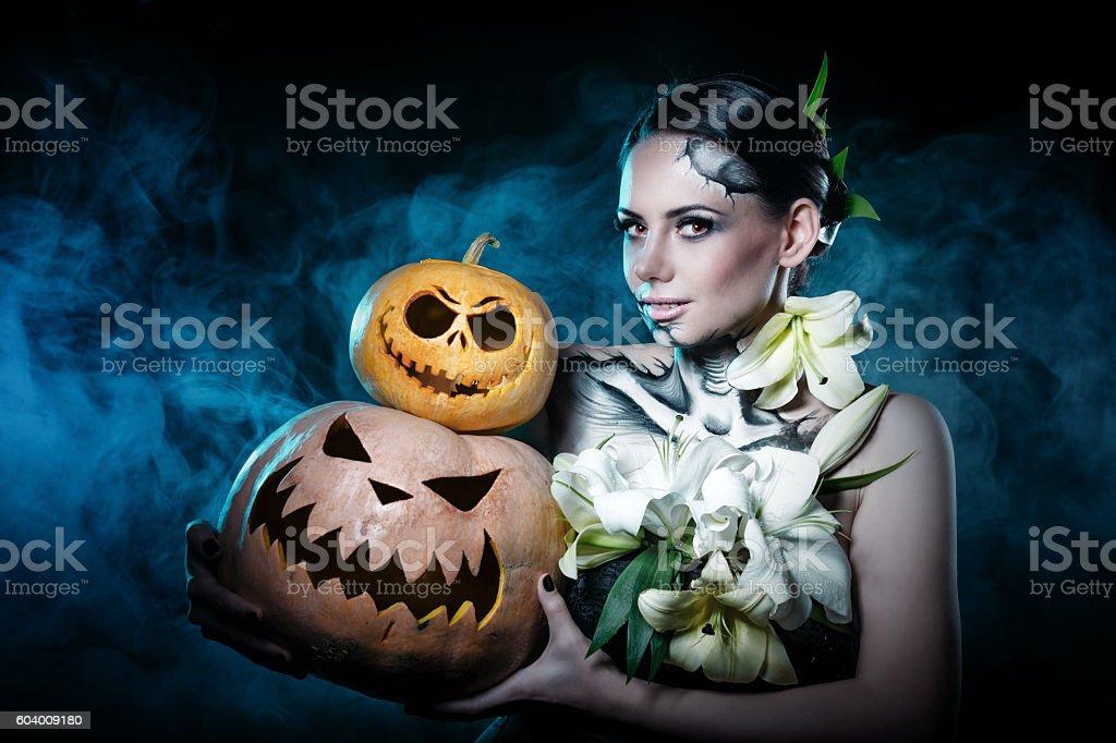 Girl with makeup for Halloween. Pumpkins stock photo
