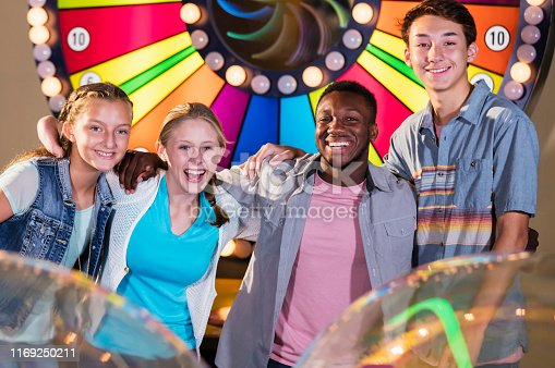 istock Girl with malformed arm, friends at amusement arcade 1169250211