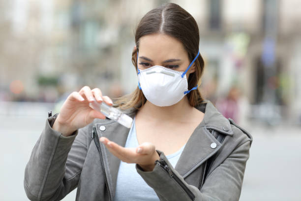 Girl with mask applying hand sanitizer on street stock photo