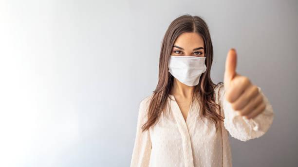 コロナウイルスから彼女を保護するためにマスクを持つ女の子。 - マスク ストックフォトと画像