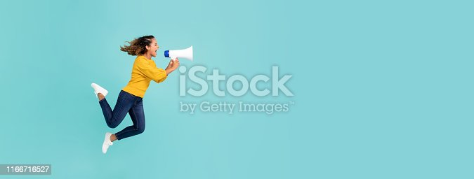 1166716628 istock photo Girl with megaphone jumping and shouting 1166716527