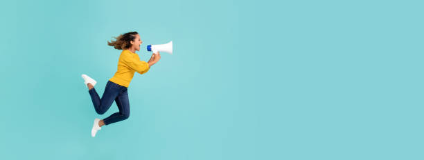 Girl with megaphone jumping and shouting stock photo