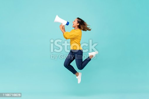 Young African American girl with megaphone jumping and shouting on light blue background