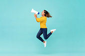 istock Girl with megaphone jumping and shouting 1166716628