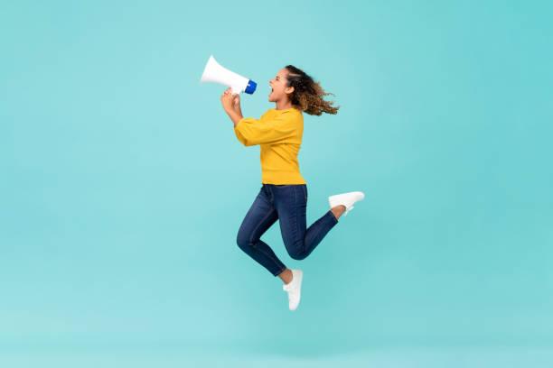 女孩與擴音器跳躍和喊叫 - 少女 個照片及圖片檔