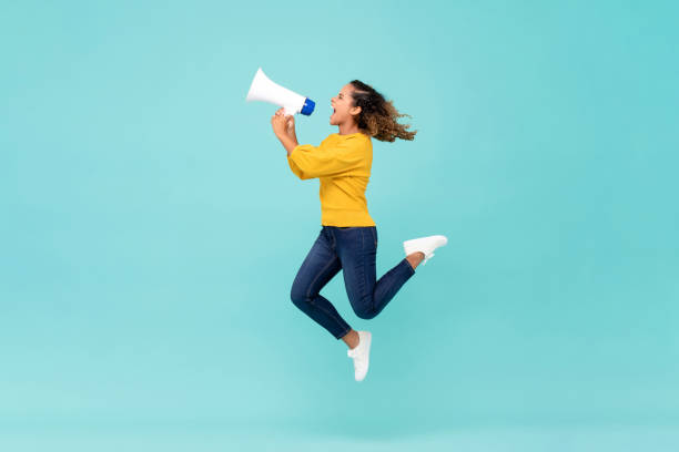 Girl with megaphone jumping and shouting Young African American girl with megaphone jumping and shouting on light blue background crying stock pictures, royalty-free photos & images