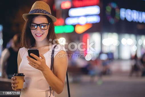 istock Girl with mobile phone and coffee in the city streets 1136872155