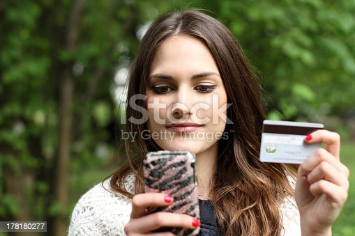 istock Girl with mobile phone and credit card shopping online  178180277
