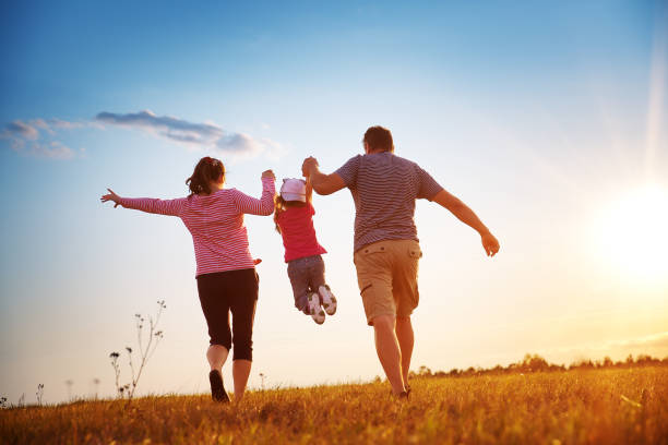 girl with mother and father holding hands on the nature stock photo