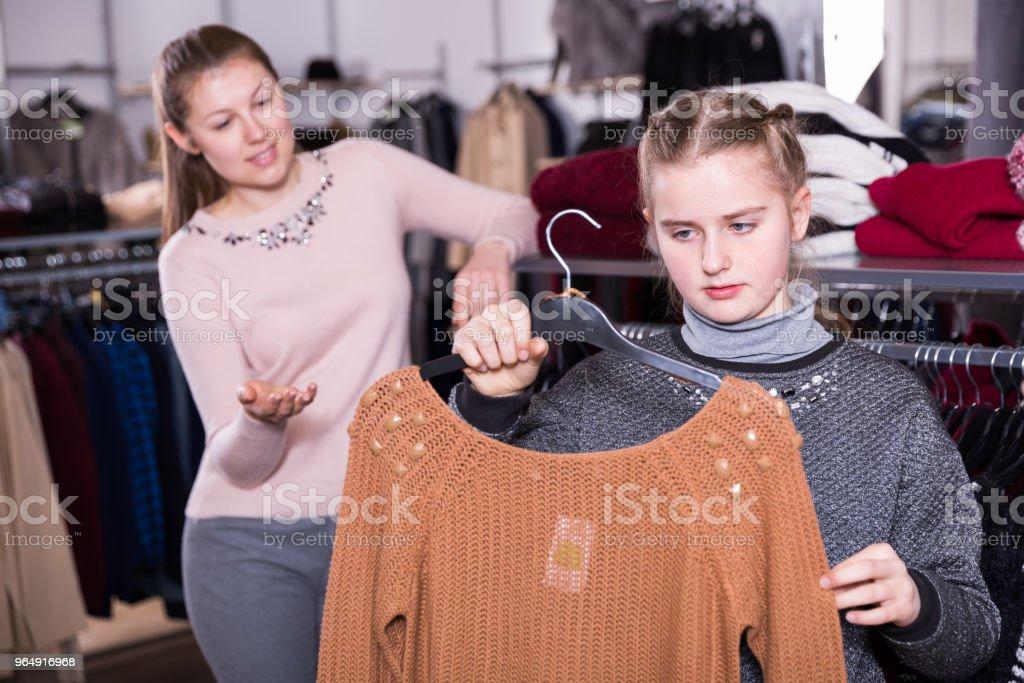 女孩與母親選擇毛衣在商店 - 免版稅一起圖庫照片