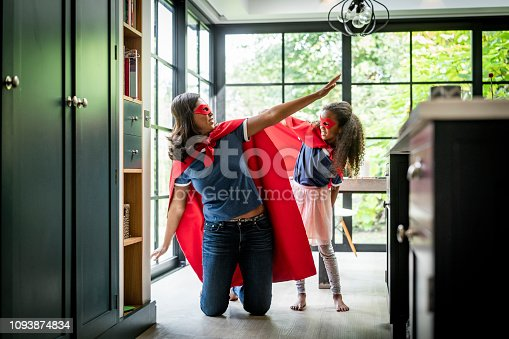 Playful mother and daughter in superhero costume against window. Woman is kneeling with arms outstretched by girl standing in kitchen. They are enjoying at home.