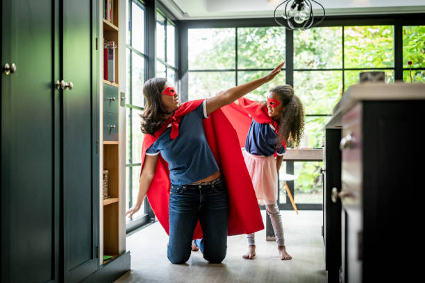 Girl with mother in red superhero costume at home Playful mother and daughter in superhero costume against window. Woman is kneeling with arms outstretched by girl standing in kitchen. They are enjoying at home. dressing up stock pictures, royalty-free photos & images