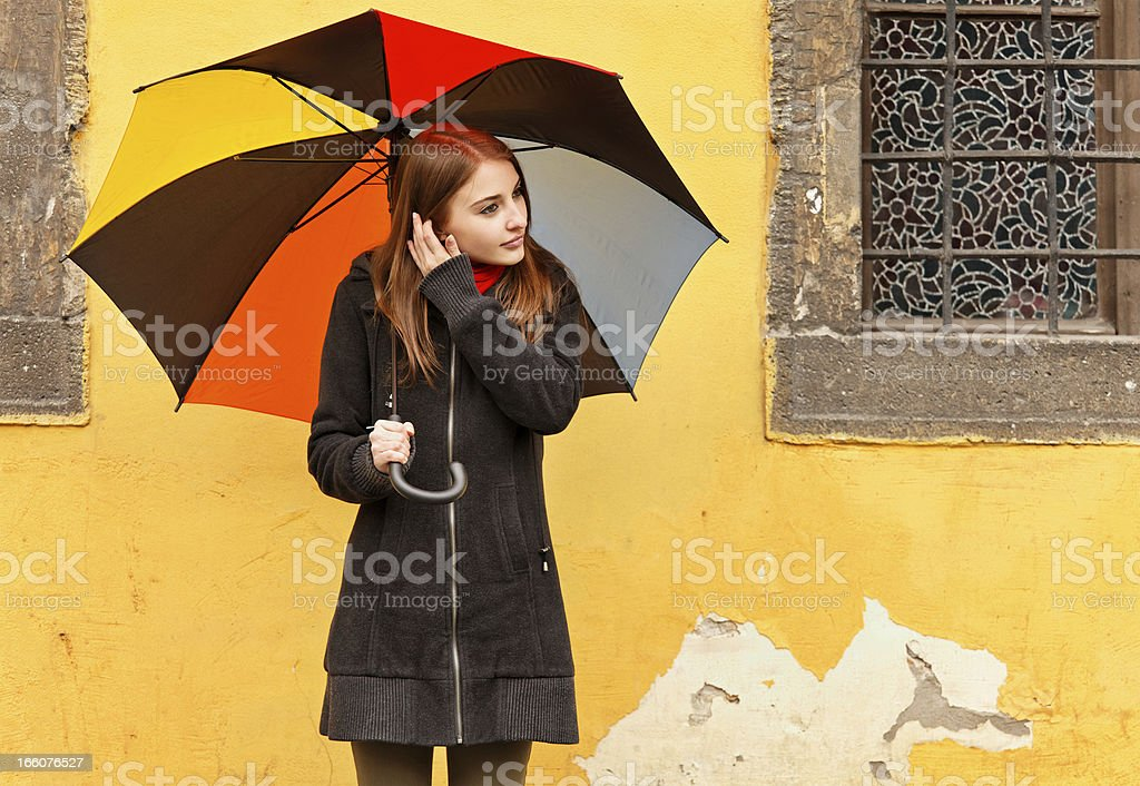 Girl with multicolored umbrella in the rain royalty-free stock photo