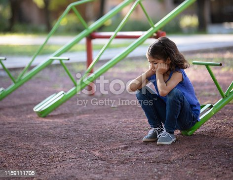 A sad little girl sitting alone on a teeter tooter with her hands on her face.