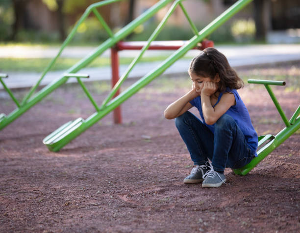 Girl with no one to play with on the teeter totter stock photo