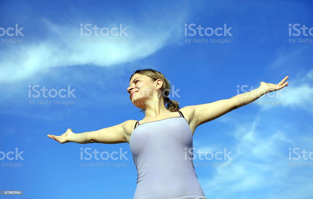 girl with open hands against the blue sky royalty free stockfoto