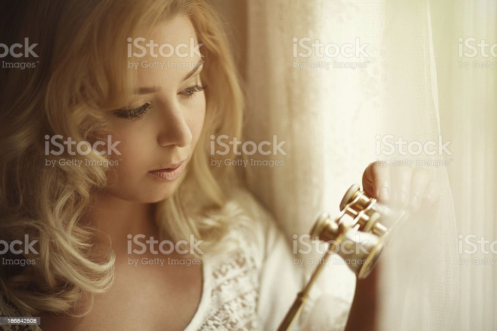 girl with opera glasses looking out of the window royalty-free stock photo