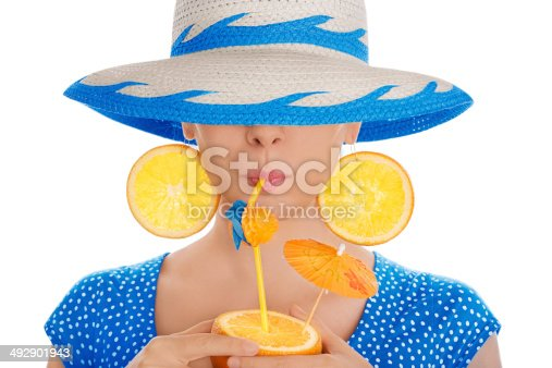 istock Girl with Orange Drink and Orange Slice Earrings Wearing Hat 492901943