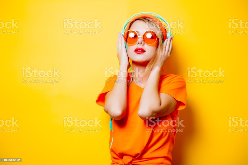 girl with orange glasses and headphones Young style girl with orange glasses and headphones on yellow background. Clothes in 1980s style 1980-1989 Stock Photo