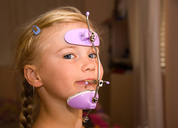 Girl with orthodontics head gear stock photo