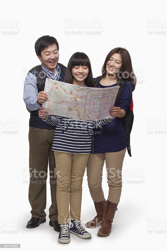 Girl with parents checking map stock photo