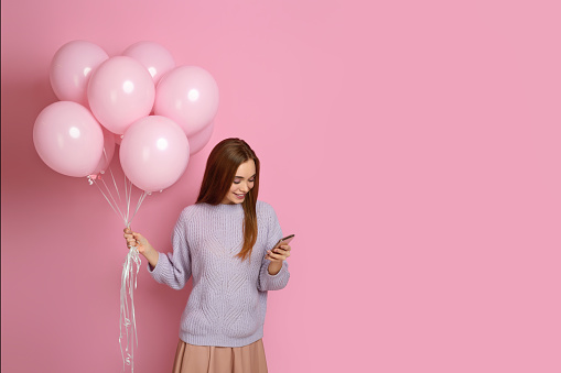 istock girl with pastel pink air balloons holding smart phone 1217602783