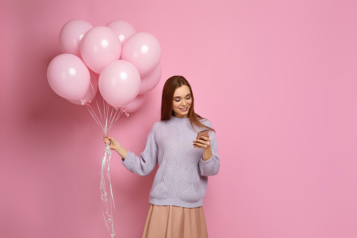 istock girl with pastel pink air balloons holding smart phone 1217602823