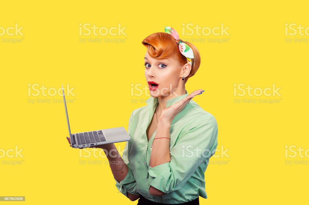 Girl with personal computer. Closeup red head beautiful young woman pretty excited, amazed smiling pinup girl green button shirt holding pc hand up looking at you camera, retro vintage 50's hairstyle stock photo