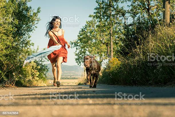 Girl with pet dog walking along road in countryside Happy brunette walking with labrador retriever dog along sunlit road Adult Stock Photo