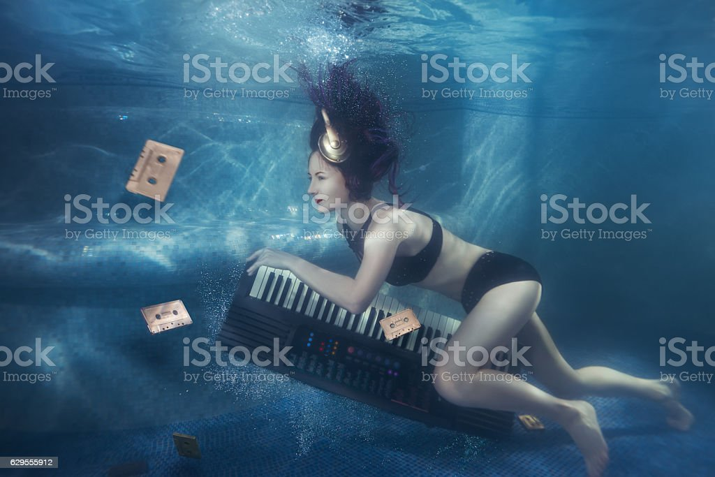 Girl with piano under water. stock photo