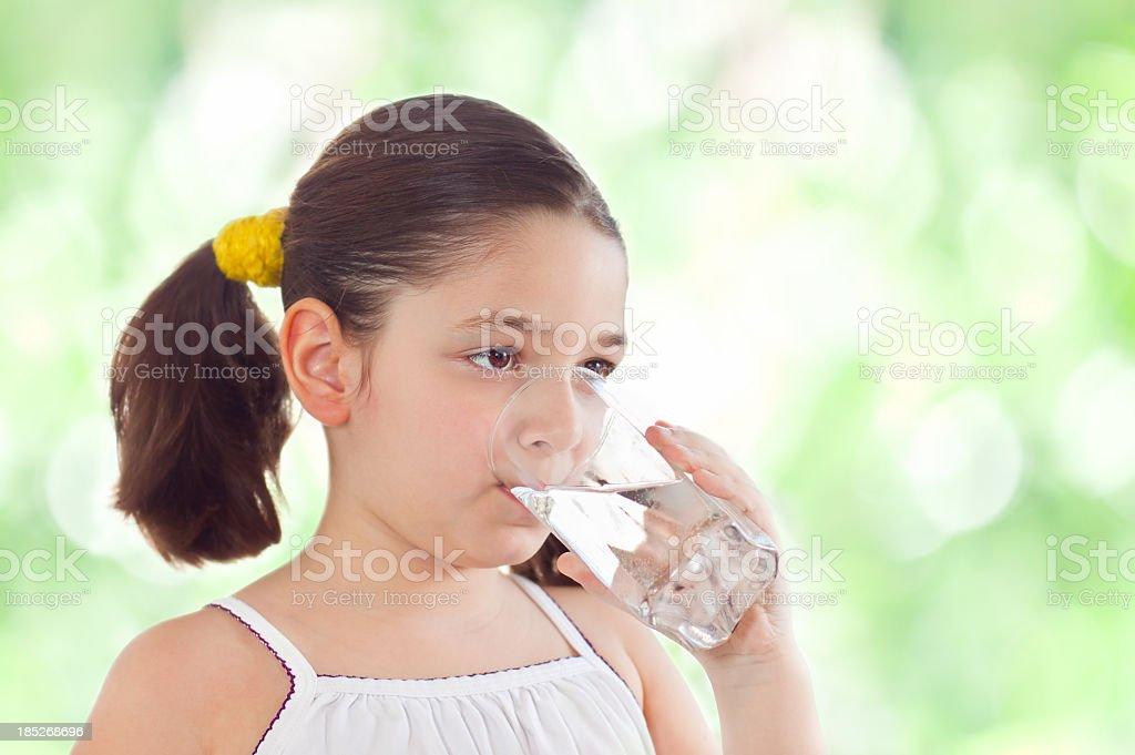 A girl with pigtails drinks a glass of water in the summer royalty-free stock photo
