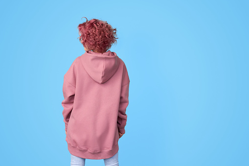 Girl with pink curly hair wearing oversized pink casual hoodie and jeans standing backwards