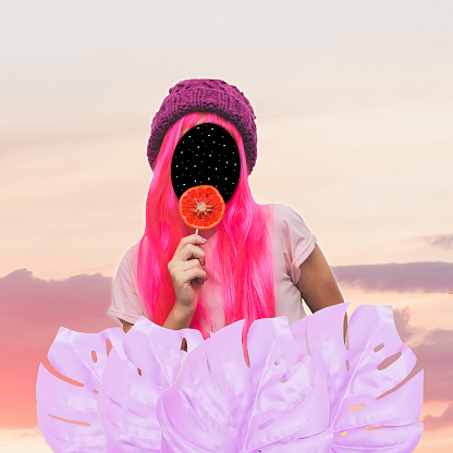 istock Girl with pink hair and space instead of a face holding an orange candy against the sky. 964255126