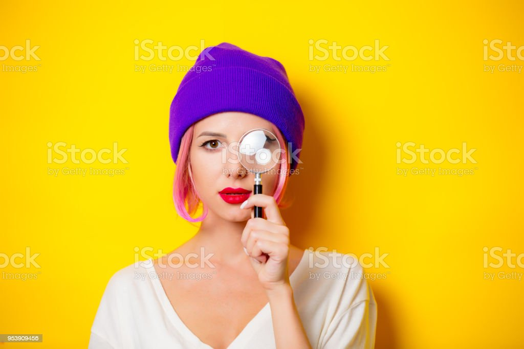 girl with pink hair holding a magnifier stock photo