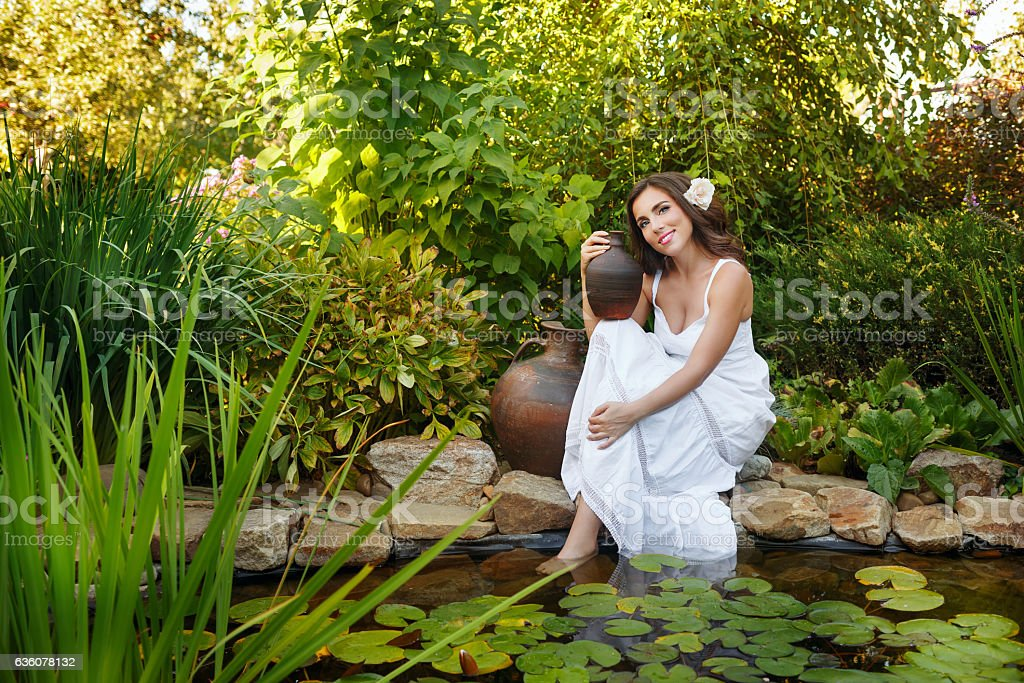 Girl with pitchers pond stock photo