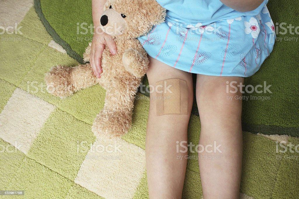 Chica con tirita en la rodilla Abrazarse Osito de peluche - foto de stock