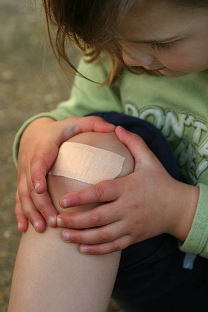 girl with plaster on knee - human knee stock photos and pictures