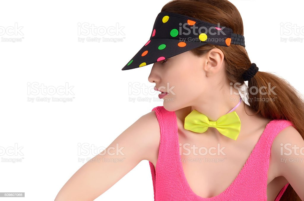 Girl with polka dots visor and bowtie looking away. stock photo